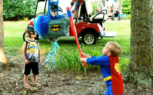Superman (John) whacking the pinata