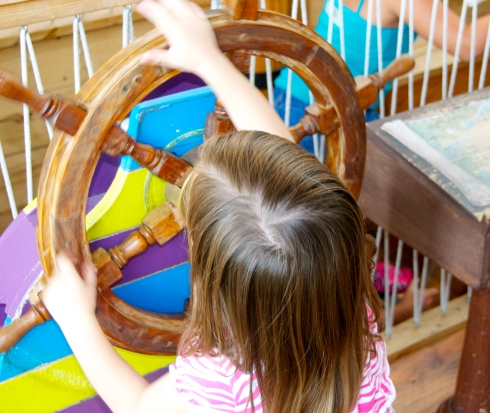 Maddie steering the pirate ship.