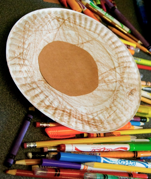 1. We colored paper plates with brown crayons, then cut out a circle of brown construction paper and glued it on.