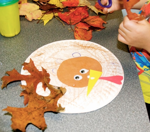 3.  We used a hot glue gun to glue on the colorful leaves that we found outside.  We snipped off the stems before glueing them on.