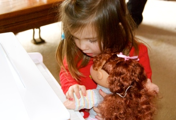 Maddie showing her new doll how to play her piano from Papa.