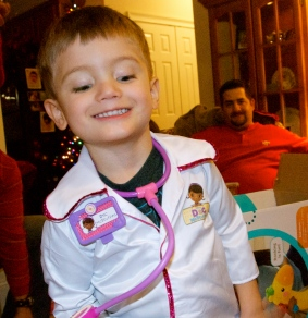 Charlie dressed as Doc McStuffins with Jason photobombing in the background.