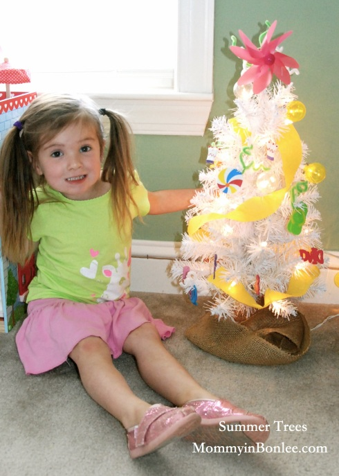 Maddie and her finished tree!  I found some great globe lights in Target, and we wrapped some yellow streamers around the tree as a finishing touch.